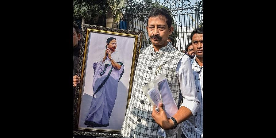 Kolkata Trinamool Congress leader Rajib Banerjee who recently exited the West Bengal cabinet carries a photograph of CM Mamata Banerjee after resigning from the post of MLA in Kolkata. (Photo | PTI)