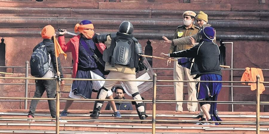 Protesters and police personnel clash at the ramparts of the Red Fort in New Delhi.
