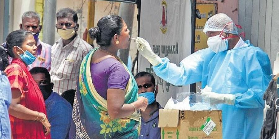A health staff taking swab sample from a woman for testing at a camp set up in Madurai. (Photo | KK Sundar, EPS)