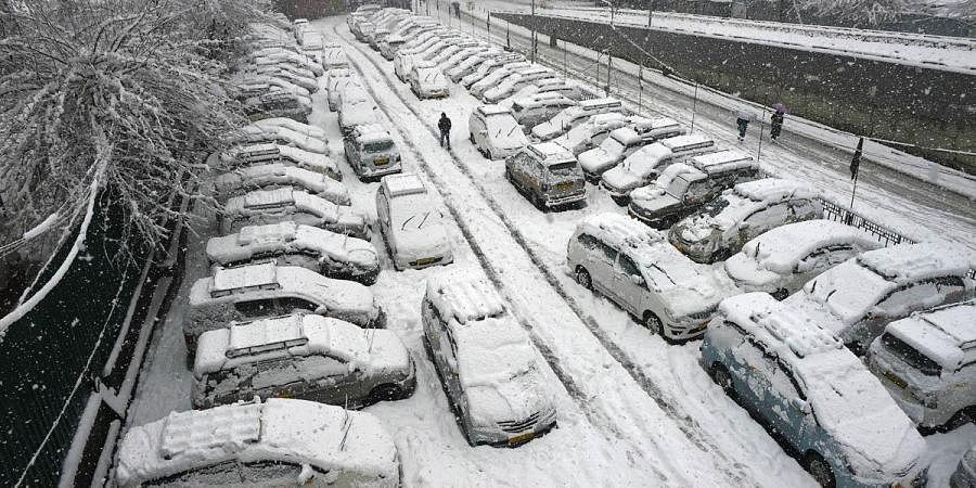 Vehicles covered under snow at a parking area during heavy snowfall, in Srinagar. (Photo | PTI)
