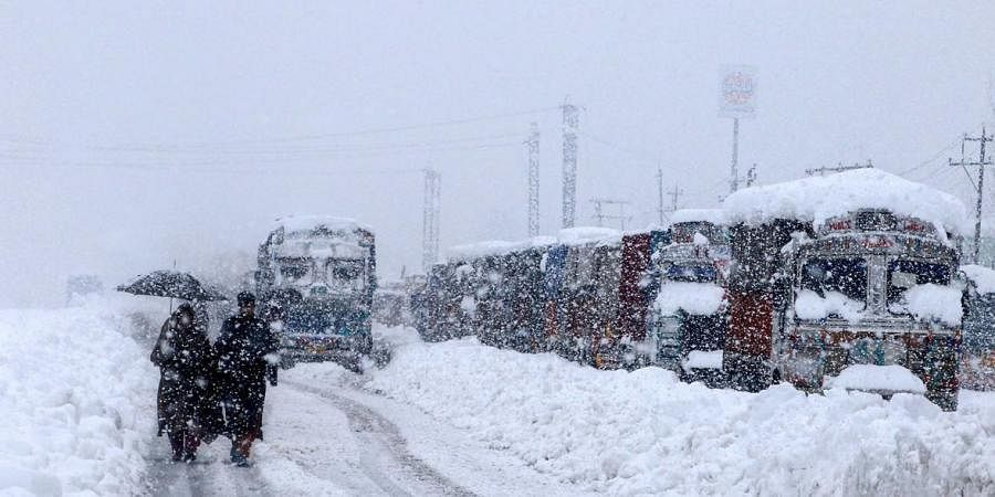 People walk past stranded vehicles on the Jammu-Srinagar National Highway during heavy snowfall, at Qazigund in Anantnagar district of South Kashmir