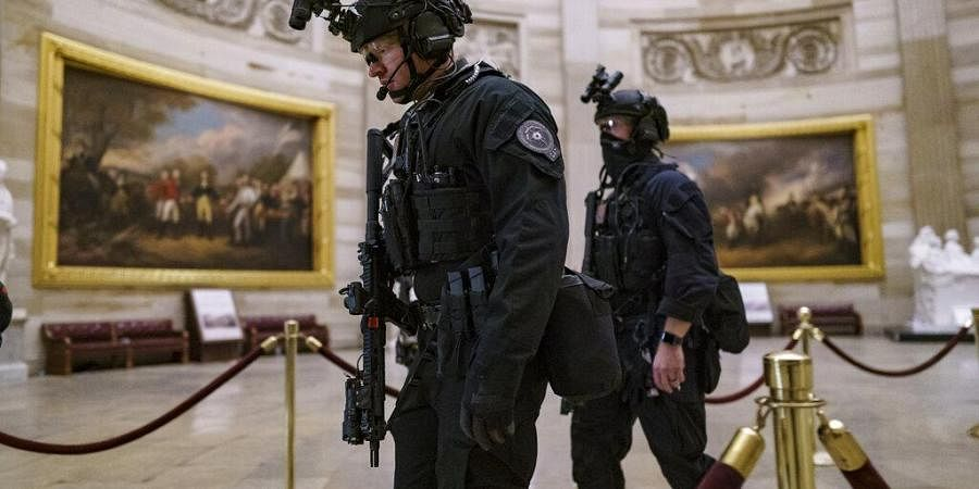 Members of the U.S. Secret Service Counter Assault Team walk through the Rotunda as response toviolent protests by Trump loyalists who stormed the Capitol.