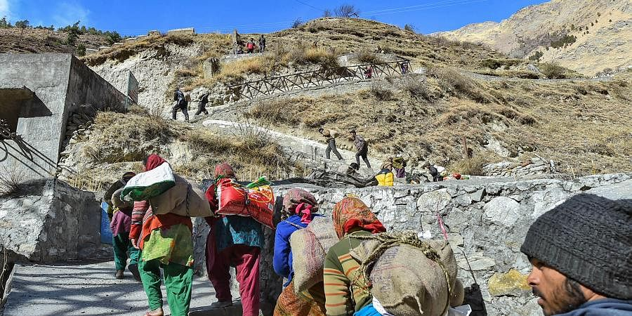 Flood-affected villagers of Bhalla gaon after receiving relief material from authorities in Chamoli district of Uttarakhand Friday