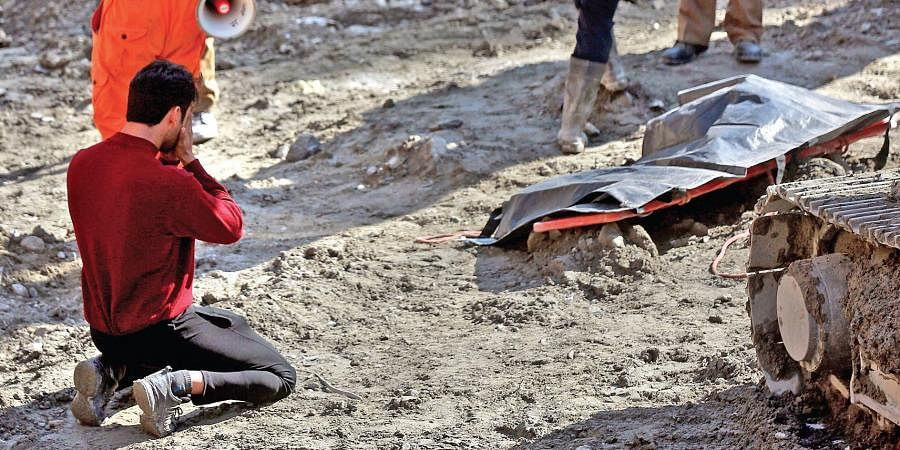 A relative of one of the victims of the Chamoli tragedy breaks down in front of his body near the Tapovan site, Uttarakhand.