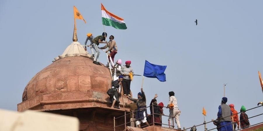 Farmers post flags on a dome of Red Fort after their tractor parade on Republic Day, in New Delhi.