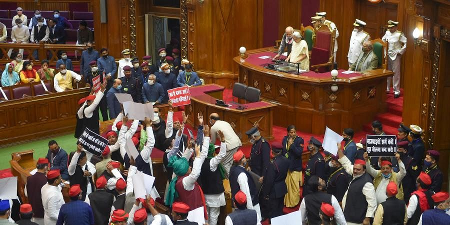 Opposition members display placards as they protest during Governor Anandiben Patel's address to the joint sitting of both the Houses on the first day of the Budget Session of the UP Assembly in Lucknow Thursday