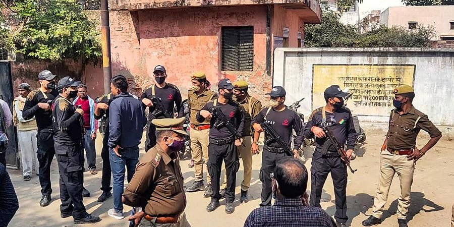 Security personnel stand guard during post-mortem of two minor Dalit girls, who were found dead in a field, near Baburaha village in Unnao district. (Photo | PTI)