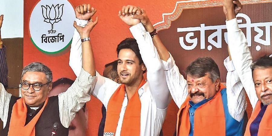 Actor Yash Dasgupta (2nd L) joins hands with BJP leaders in Kolkata