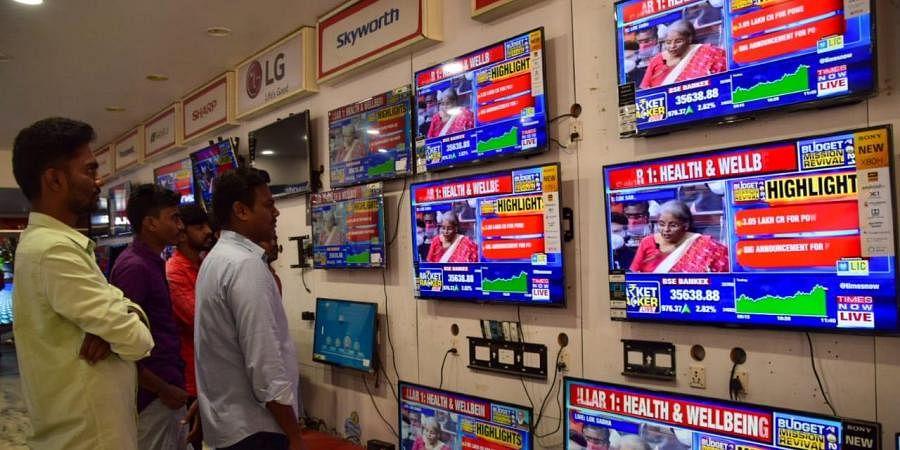 People watch Finance Minister Nirmala Sitharaman presenting Union Budget 2021-21 on television sets at an electronics store in Tirunelveli. (Photo | V Karthikalagu, EPS)