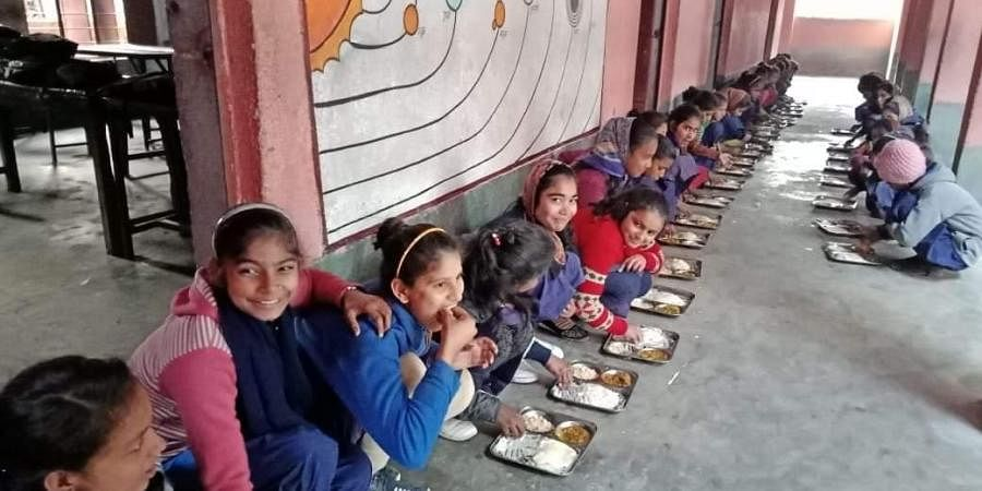Children of Sahori Government school in Vaishali district of Bihar having mid-day meal under the supervision of principal Alok Ranjan.