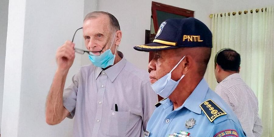 A police officer escorts Richard Daschbach, center, a former missionary from Pennsylvania, U.S. upon his arrival for a trial at a courthouse in Oecusse, East Timor