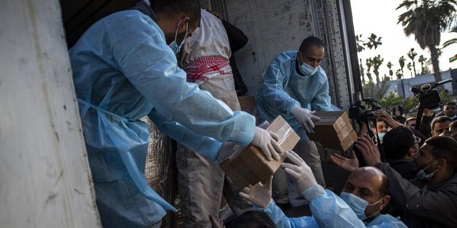Palestinian workers unload a truck from 20,000 doses of Russian-made Sputnik V vaccine upon its arrival to Gaza Strip, at the Rafah crossing border with Egypt