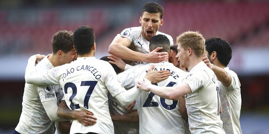 Manchester City players celebrate after Raheem Sterling scored his side's opening goal during match against Arsenal at the Emirates stadium in London, England, Sunday, Feb. 21, 2021.