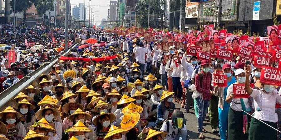 Anti-coup protesters fill the main road during a rally in Mandalay, Myanmar