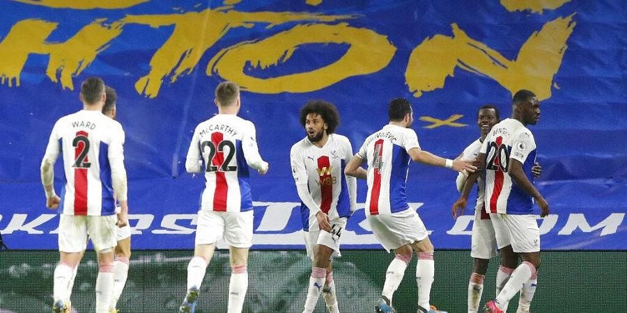 Crystal Palace players celebrate after Christian Benteke, right, scored his side's second goal during the match against Brighton at the Falmer stadium in Brighton, England, Monday.