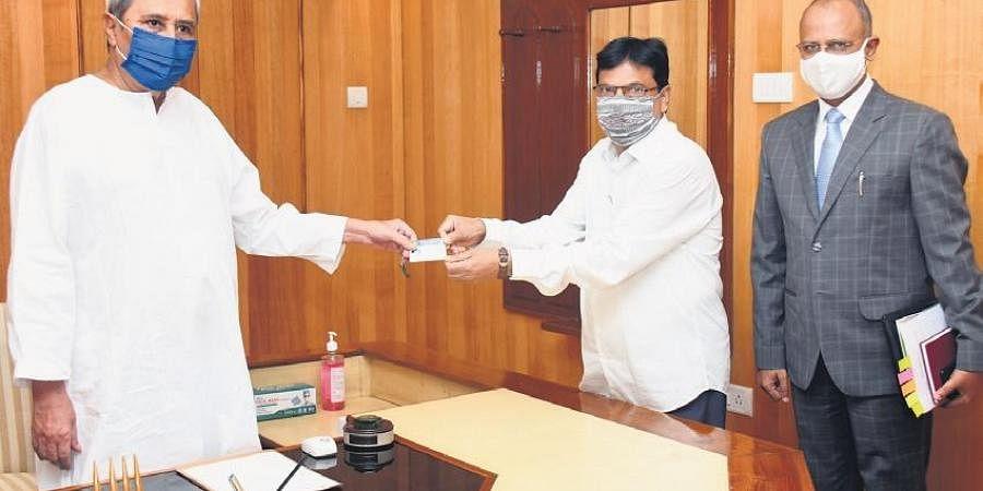 CM Naveen Patnaik receives a pen drive containing Odisha Budget 2021-22 from FM Niranjan Pujari at his Assembly chamber on Monday, along with Finance Secretary AKK Meena.