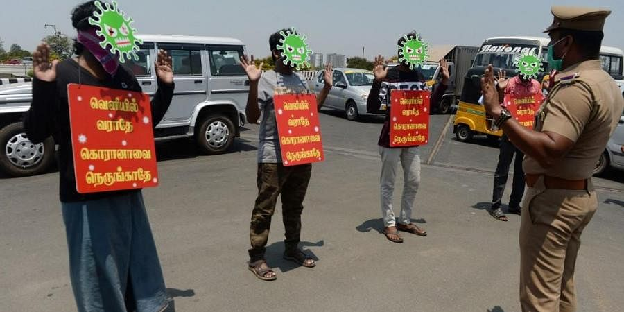Men wear masks depicting a coronavirus and placards as a punishment enforce by the police. (Photo| AFP)