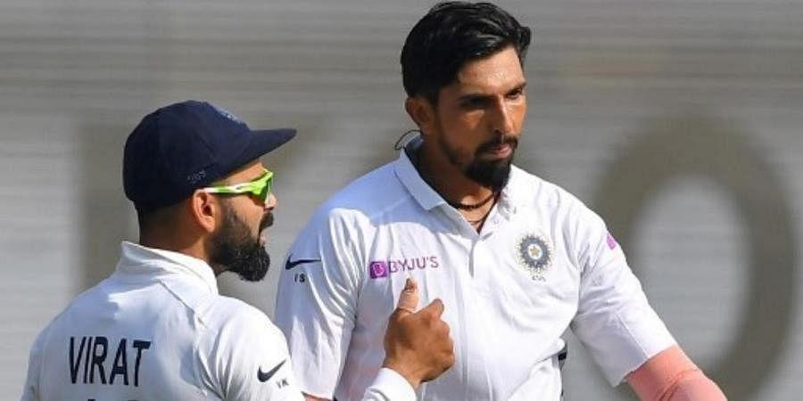 Indian skipper Virat Kohli (L) speaks to teammate Ishant Sharma