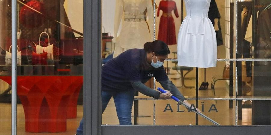 A woman wearing a face covering due to the COVID-19 pandemic cleans inside a shop during lockdown in London, Wednesday, Feb. 17, 2021. (Photo | AP)