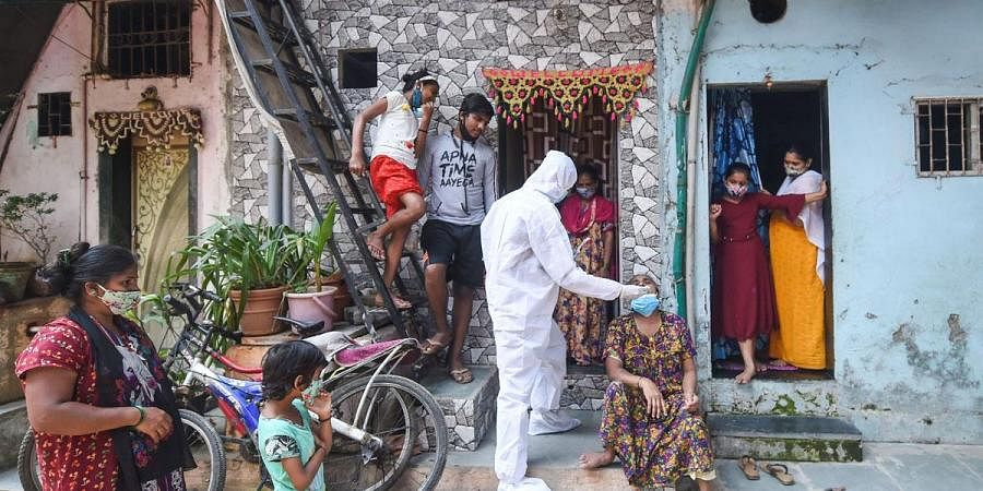 A BMC health worker wearing protective gear takes a swab sample of a woman for the COVID-19 test at Dharavi, in Mumbai