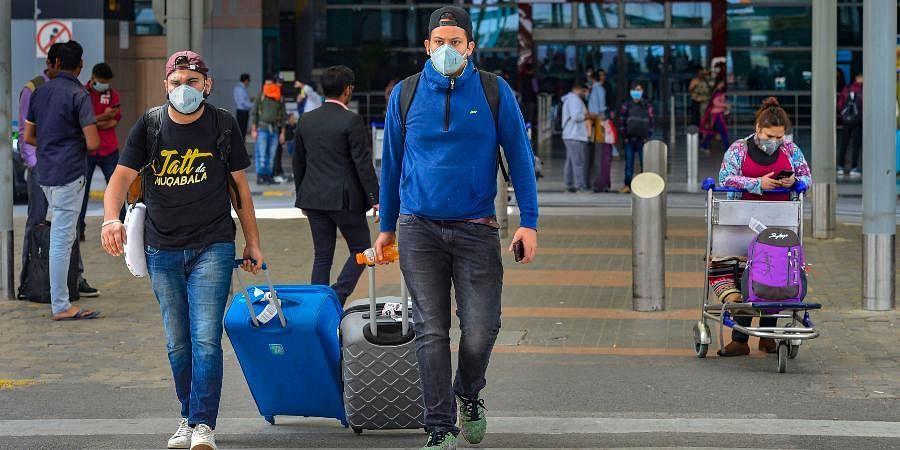 Passengers wear masks in the wake of Coronavirus pandemic at Indira Gandhi International Airport in New Delhi.