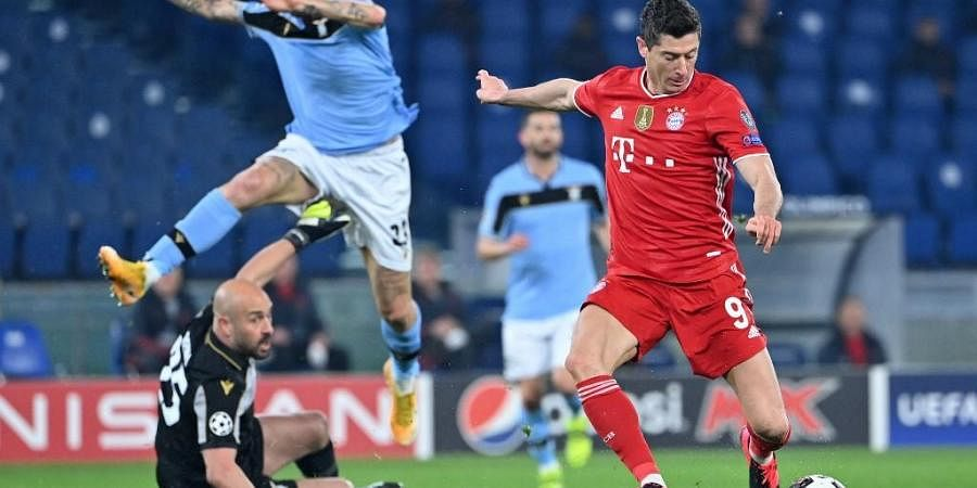 Bayern Munich forward Robert Lewandowski (R) prepares to shoot and open the scoring during the UCL match against Lazio Rome on February 23, 2021 at the Olympic stadium in Rome.