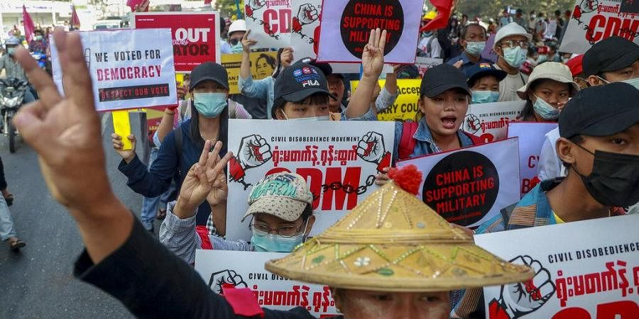 Anti-coup protesters flash the three-fingered salute in Yangon, Myanmar