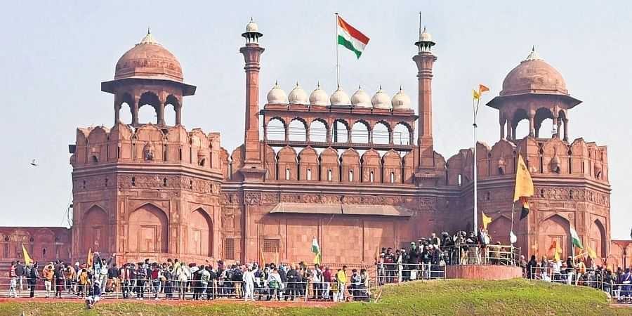 Farmers and their supporters hoist the Nishan Sahib on the ramparts of the Red Fort after they forcibly entered the 17th century monument in New Delhi.
