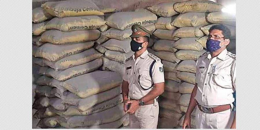 Policemen at the fake cement manufacturing unit at Jagatpur
