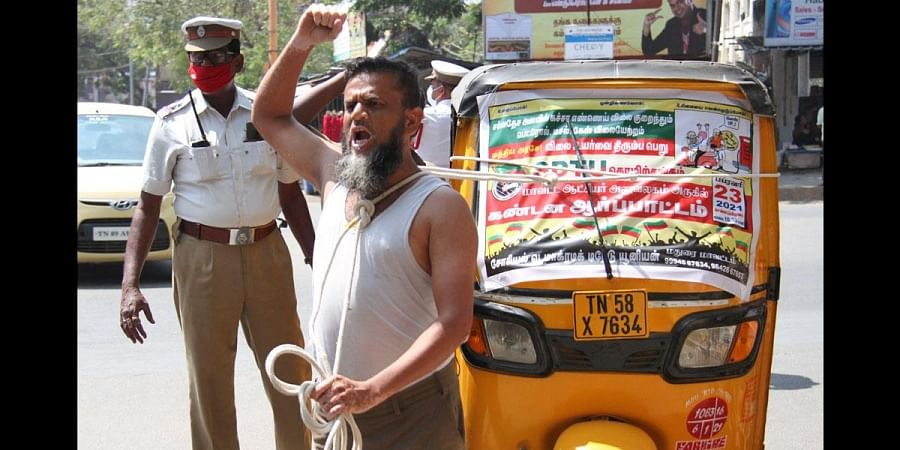 A protestor pulling the auto with a rope, condemning the petrol and diesel price hike at Collectorate in Madurai. (Photo | K K Sundar, EPS)