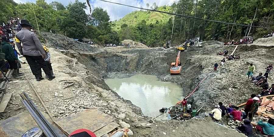 Rescuer workers pump water out of a collapsed gold mine as they search for victims in Parigi Moutong