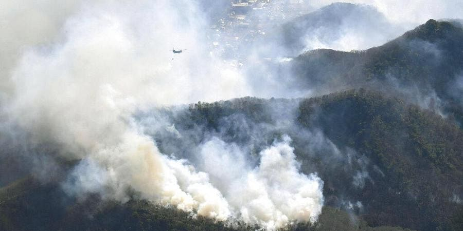 A helicopter dumps water on a wildfire in Ashikaga, Tochigi prefecture, north of Tokyo