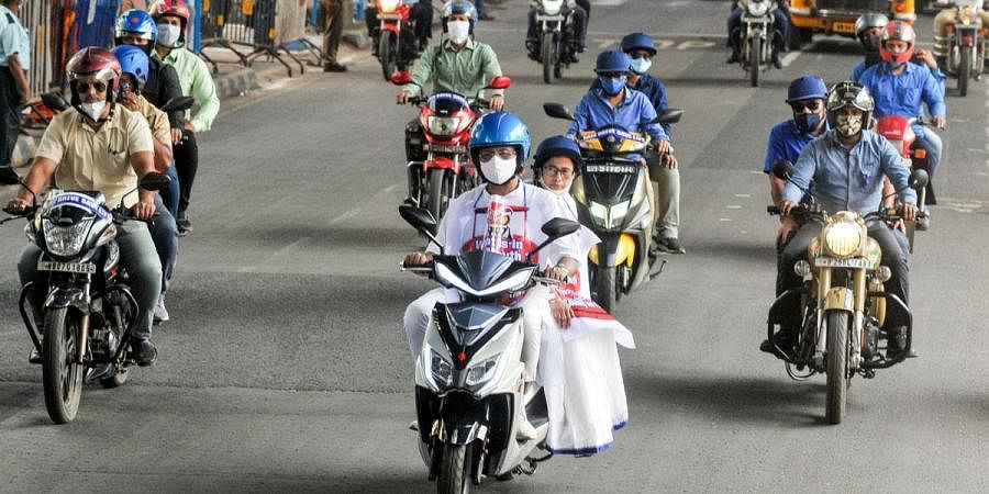 Chief Minister Mamata Banerjee rides pillion on an electric scooter to reach during a protest against the hike in fuel price, in Kolkata. (Photo | PTI)