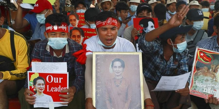 Protesters display images of deposed Myanmar leader Aung San Suu Kyi as they take part in a demonstration against the military coup in Yangon