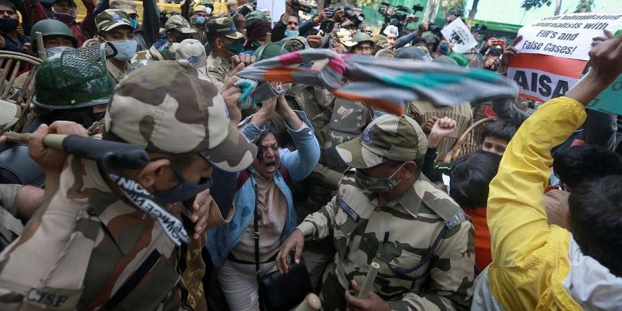 Woman folds her hands in front of security at a protest showing solidarity with farmers protesting against farm laws in New Delhi