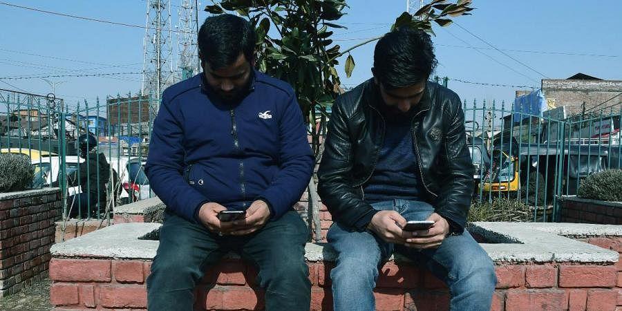 Kashmiri boys use mobile phones after restoration of 4G mobile internet, in Srinagar