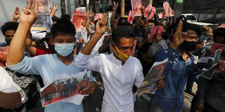 Myanmar nationals living in Thailand hold pictures of Myanmar leader Aung San Suu Kyi gesture with a three-fingers salute, a symbol of resistance