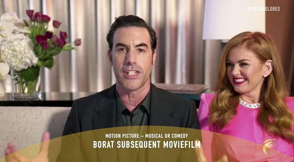 acha Baron Cohen, left, accepts the award for best picture, musical or comedy, for 'Borat Subsequent Moviefilm' as his wife Isla Fisher looks on. (Photo | AP)
