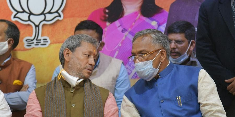 BJP leader Tirath Singh Rawat L interacts with outgoing CM Trivendra Singh Rawat after he was elected as new Chief Minister of Uttarakhand in Dehradun Wednesday