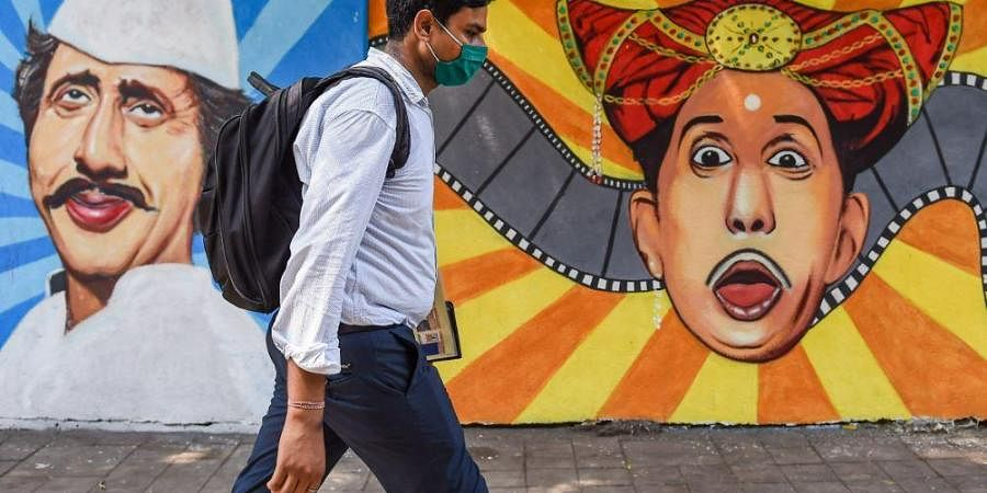 A man wearing a face mask as a precaution against Covid-19 walks past a mural at Lalbaug in Mumbai