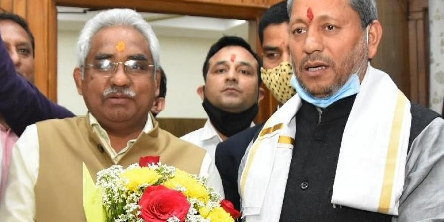 Chief Minister Tirath Singh Rawat meets BJP State President Madan Kaushik after his appointment. (Photo  EPS)
