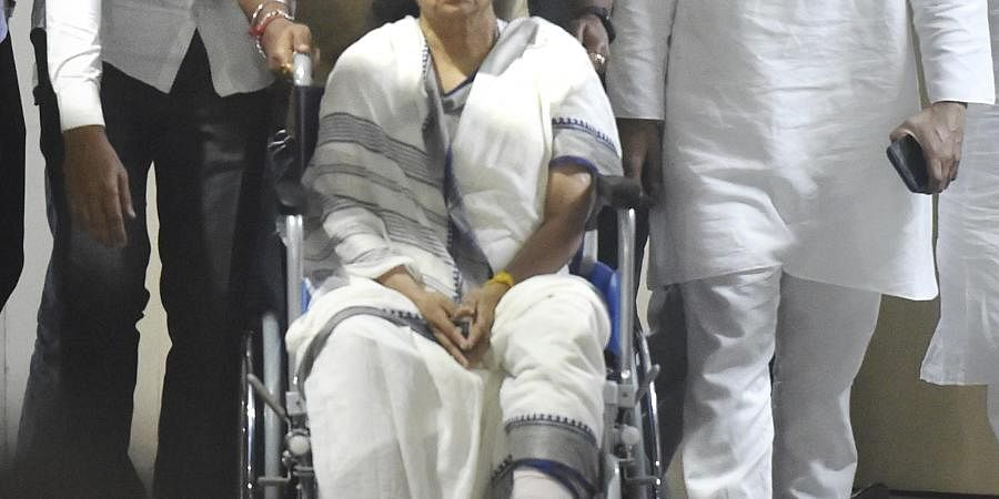 West Bengal Chief Minister Mamata Banerjee sitting in a wheel-chair being discharged from SSKM Hospital in Kolkata Friday March 12 2021.