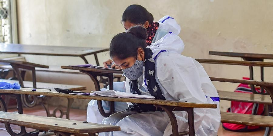 Final year students of BBA and B. Com courses write their exams wearing PPE kits, at Maharani College of Arts & Science, in Bengaluru