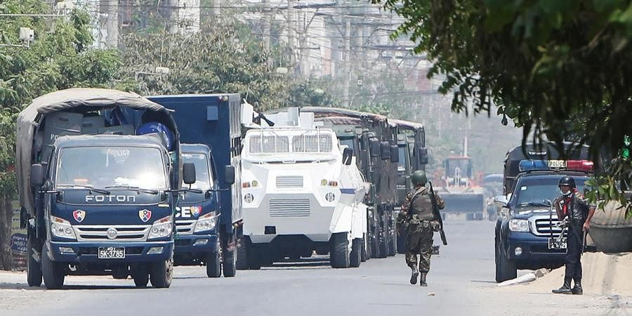 A soldier walks along a row of vehicles by security forces parked on a road in Mandalay, Myanmar