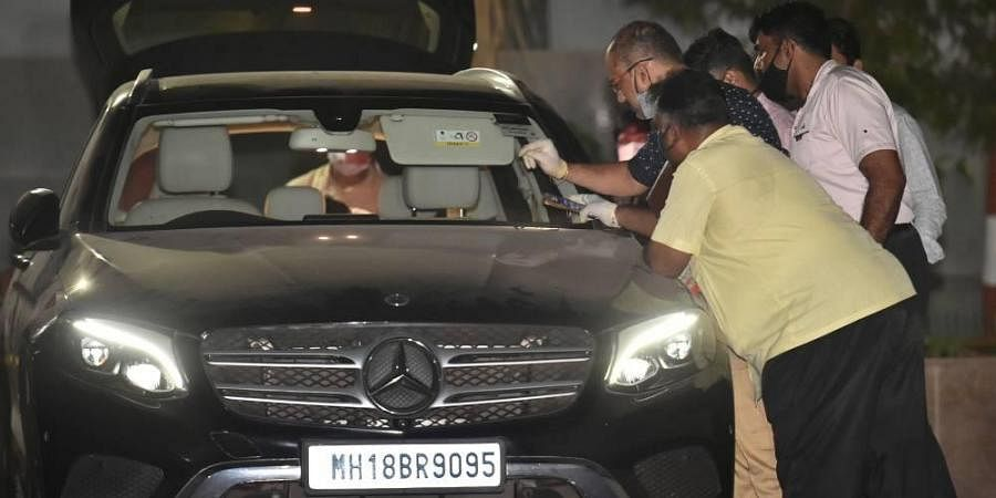 NIA officers investigate Sachin Vaze's Mercedes car, in connection with a probe into the recovery of explosives from a car parked near Mukesh Ambanis house. (Photo | PTI)