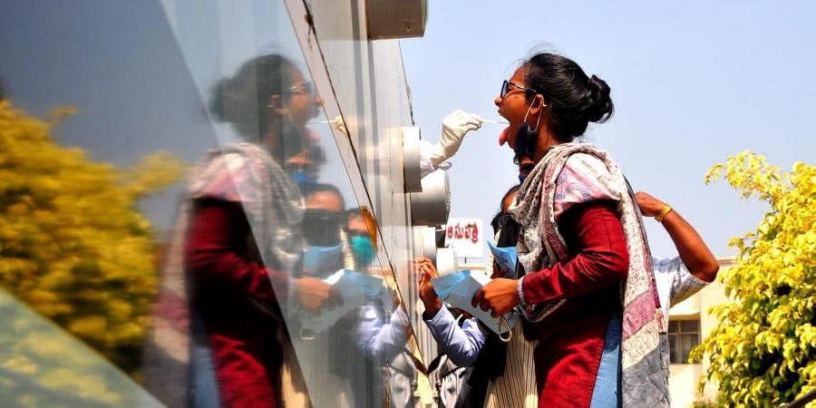 People give their swab samples for Covid-19 test at Sanjeevini bus at ENT hospital in Visakhapatnam on Monday.