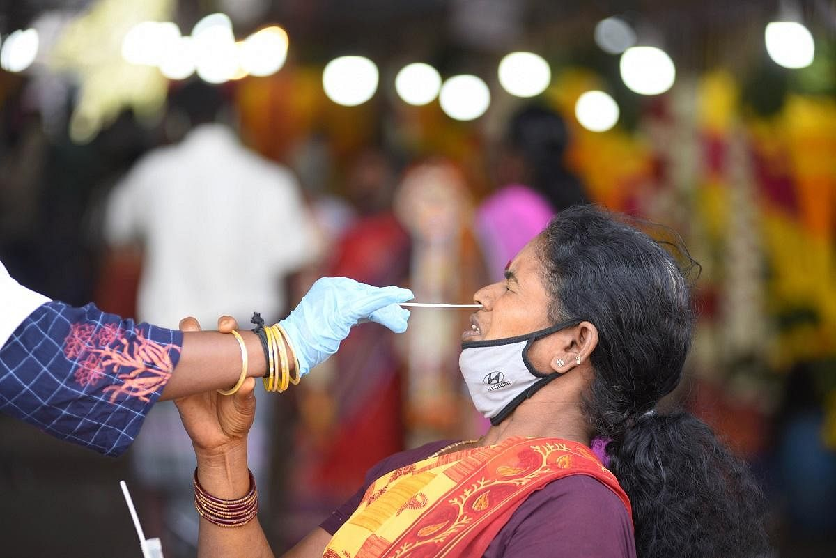 A health worker collects samples from a woman at Koyambedu Flower Market in Chennai. (Photo | R Satish Babu, EPS)