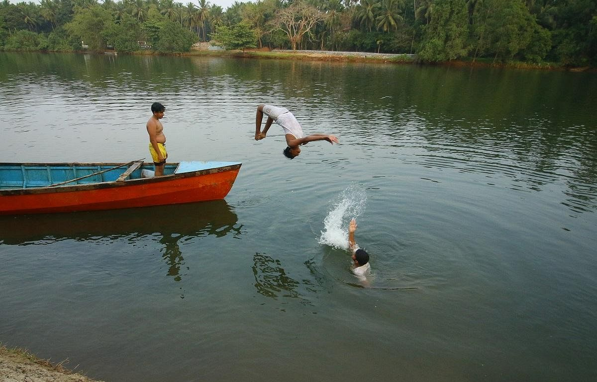 A group of boys enjoy a dip in the river to beat the summer heat at Perinjerikadavu in Kozhikode. (Photo | T P Sooraj, EPS)