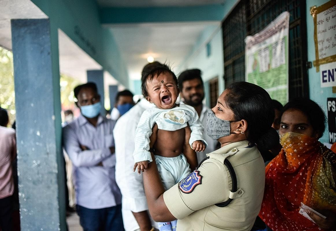 A police officer taking care of a baby while her mother casting vote for MLC elections in Hyderabad. (Photo | Vinay Madapu, EPS)