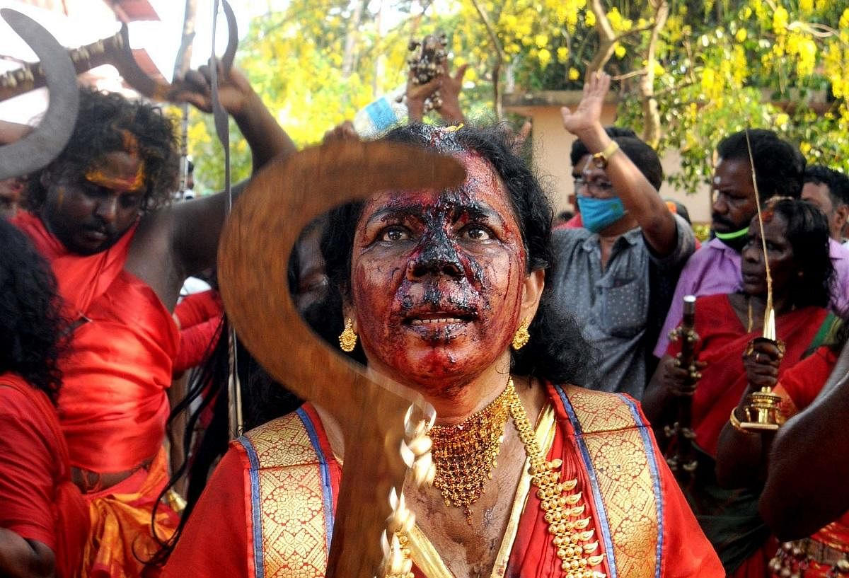 Blood trickles down the face of an oracle after she cut her head with a sword as a sacrificial offering at Sree Kurumba Bhagavathy Temple in Kodungallur, as part of the Bharani festival. (Photo | A Sanesh, EPS)